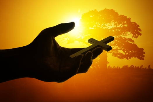 Silhouette Hand holding cross on nature background
