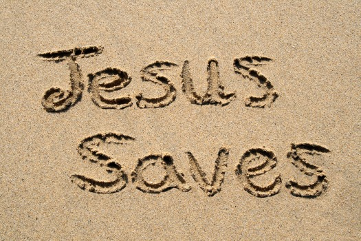 Jesus saves, written on a sandy beach.