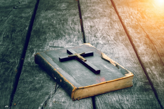 Closeup of wooden Christian cross on bible on the old table. Church utensils.