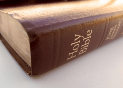 Side view of the Holy Bible, burgundy leather bible with gold lettering and gold pages. Great religious image for Christian or Catholic Church, Pastor or Bible Study
