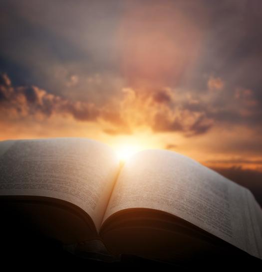 Open old book, light from the sunset sky, heaven. Fantasy, imagi